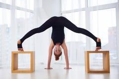 La bella giovane donna pratica il asana Prasarita Padottanasana di yoga allo studio di yoga Immagine Stock