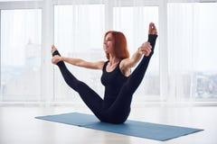 La bella giovane donna pratica il asana Urdhva Upavistha Konasana di yoga allo studio di yoga Immagini Stock