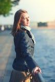 La bella giovane donna in sciarpa gode della luce solare nella città Immagine Stock