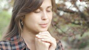 La bella giovane donna si gira verso Dio con le sensibilità nella preghiera, la ragazza ha piegato le sue armi al suo petto e con stock footage