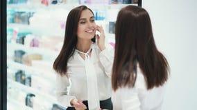 La bella giovane donna si pavoneggia davanti allo specchio in deposito cosmetico