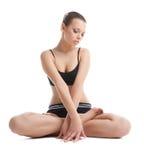 La bella giovane donna si siede nella posa di yoga di lotos fotografia stock