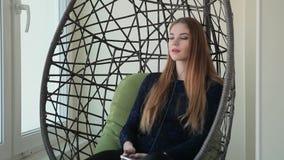 La bella giovane donna si siede in una sedia del pendente con il telefono ed ascolta musica video d archivio