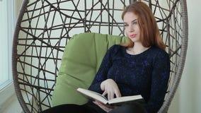 La bella giovane donna si siede in una sedia del pendente con la tazza di tè o di caffè caldo video d archivio