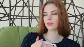 La bella giovane donna si siede in una sedia del pendente con la tazza di tè o caffè e sogno caldi stock footage