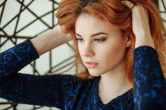 La bella giovane donna si siede in una sedia del pendente nella stanza fotografia stock libera da diritti