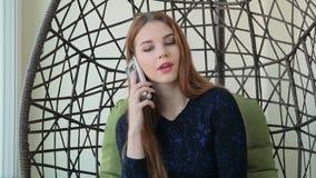 La bella giovane donna si siede in una sedia e nella conversazione sul telefono archivi video