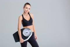 La bella giovane donna sorridente di forma fisica nella tenuta della tuta sportiva pesa la scala Fotografia Stock