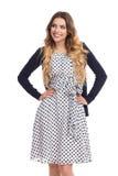 La bella giovane donna sorridente in vestito ed in cardigan punteggiati sta distogliendo lo sguardo Immagine Stock Libera da Diritti