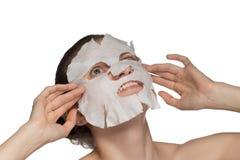 La bella giovane donna sta applicando una maschera cosmetica su un fronte su un fondo bianco fotografia stock libera da diritti