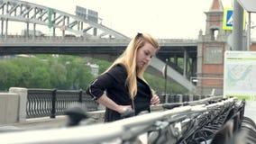 La bella giovane donna sta camminando in città e prende la bicicletta per affitto video d archivio