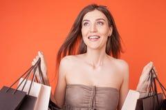 La bella giovane donna sta comprando le cose con Immagini Stock Libere da Diritti