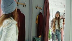 La bella giovane donna sta provando sui vestiti nella stanza adatta Sta guardandosi in specchio, nella posa e nel muoversi stock footage
