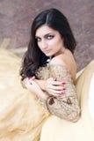 La bella giovane donna sta sedendosi Fotografia Stock