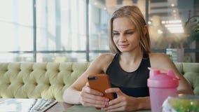 La bella giovane donna sta sedendosi allo scrittorio e sta facendo il selfie sulla macchina fotografica dello smartphone video d archivio