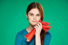 La bella giovane donna su un fondo verde tiene i guanti di gomma, la pulizia, lavoro domestico immagini stock