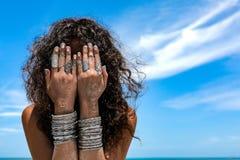 La bella giovane donna sui precedenti della spiaggia riguarda il suo spirito del fronte Immagine Stock Libera da Diritti