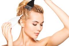 La bella giovane donna tinge i suoi capelli Fotografia Stock