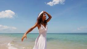 La bella giovane donna in una corona bianca del fiore e del vestito funziona a piedi nudi lungo il litorale e si gode di che fila archivi video