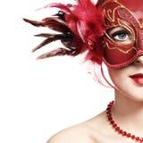 La bella giovane donna in una mascherina veneziana rossa Fotografie Stock Libere da Diritti