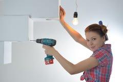 La bella giovane donna utilizza un trapano elettrico Fotografia Stock