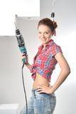 La bella giovane donna utilizza un trapano elettrico Immagine Stock