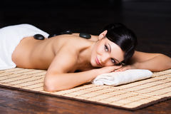 La bella, giovane e donna in buona salute sulla stuoia di bambù nel salone della stazione termale sta avendo massaggio di pietra  immagini stock