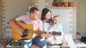 La bella giovane famiglia che spende il tempo nella cucina, il padre gioca la chitarra video d archivio