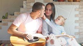 La bella giovane famiglia che spende il tempo nella cucina, il padre gioca la chitarra stock footage