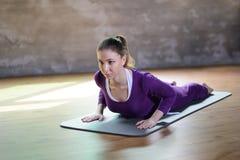 La bella giovane femmina atletica fa la cobra del mezzo di asana di yoga Fotografia Stock