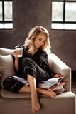 La bella giovane femmina bionda allegra in pigiami gode del caffè di mattina, legge il libro come prepara per la presentazione, s Fotografie Stock Libere da Diritti