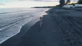 La bella giovane femmina funziona lungo la spiaggia dell'oceano con la sabbia nera ed ondeggia al tramonto su Bali, il video 4K d archivi video