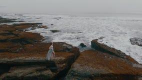 La bella giovane femmina in un vestito sexy lungo posa sulle rocce sulla spiaggia dell'oceano su Bali sul tramonto, il video 4K d stock footage