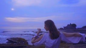 La bella giovane femmina in un vestito sexy lungo sta sulle rocce sulla spiaggia dell'oceano su Bali sul tramonto con la vista me video d archivio