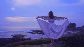 La bella giovane femmina in un vestito sexy lungo sta sulle rocce sulla spiaggia dell'oceano su Bali sul tramonto con la vista me archivi video