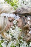 La bella giovane madre con sua figlia si è vestita nei vestiti di primavera e corone dei fiori Fotografia Stock