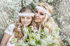 La bella giovane madre con sua figlia si è vestita nei vestiti di primavera e corone dei fiori Immagine Stock Libera da Diritti