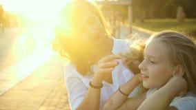 La bella giovane madre e sua figlia si divertono nel parco La madre prende la cura di sua figlia, raddrizza i suoi capelli a video d archivio