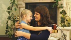 La bella giovane madre e sua figlia stanno abbracciando e sorridendo stock footage