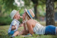 La bella giovane madre ed suo figlio stanno divertendo all'aperto in sole Giorno di madre immagini stock libere da diritti