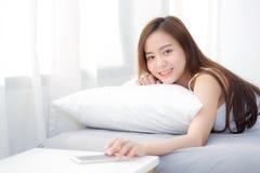 La bella giovane mano asiatica della donna di spegne l'allarme sul telefono cellulare di chiamata mentre svegli dopo sonno immagine stock libera da diritti