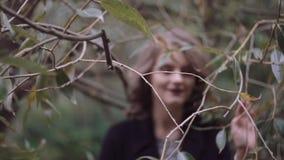 La bella giovane ragazza bionda alla moda guada attraverso i rami degli alberi, esaminare la macchina fotografica Movimento lento video d archivio