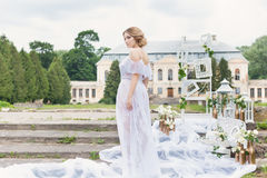 La bella giovane ragazza bionda dolce con il mazzo di nozze nelle mani del boudoir in un vestito bianco con l'acconciatura di ser immagini stock libere da diritti