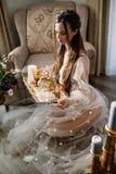 La bella giovane ragazza bionda dolce con un mazzo di nozze nelle mani del boudoir in un vestito bianco con l'acconciatura di ser Fotografia Stock