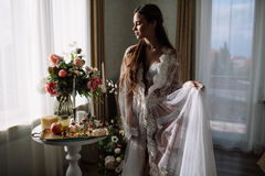 La bella giovane ragazza bionda dolce con un mazzo di nozze nelle mani del boudoir in un vestito bianco con l'acconciatura di ser Fotografia Stock Libera da Diritti