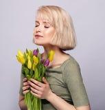 La bella giovane ragazza bionda respira il profumo dei fiori della molla fotografia stock libera da diritti
