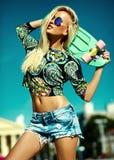 La bella giovane ragazza di modello bionda nei pantaloni a vita bassa dell'estate copre con il pattino Fotografie Stock
