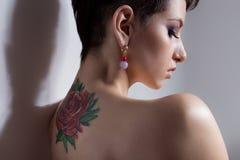 La bella giovane ragazza sexy con i capelli di scarsità con il tatuaggio sul suo indietro è contro la parete con le spalle nude t immagini stock libere da diritti