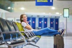 La bella giovane ragazza turistica con lo zaino e continua i bagagli in aeroporto internazionale Fotografia Stock Libera da Diritti