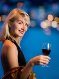 La bella giovane signora beve il vino immagine stock